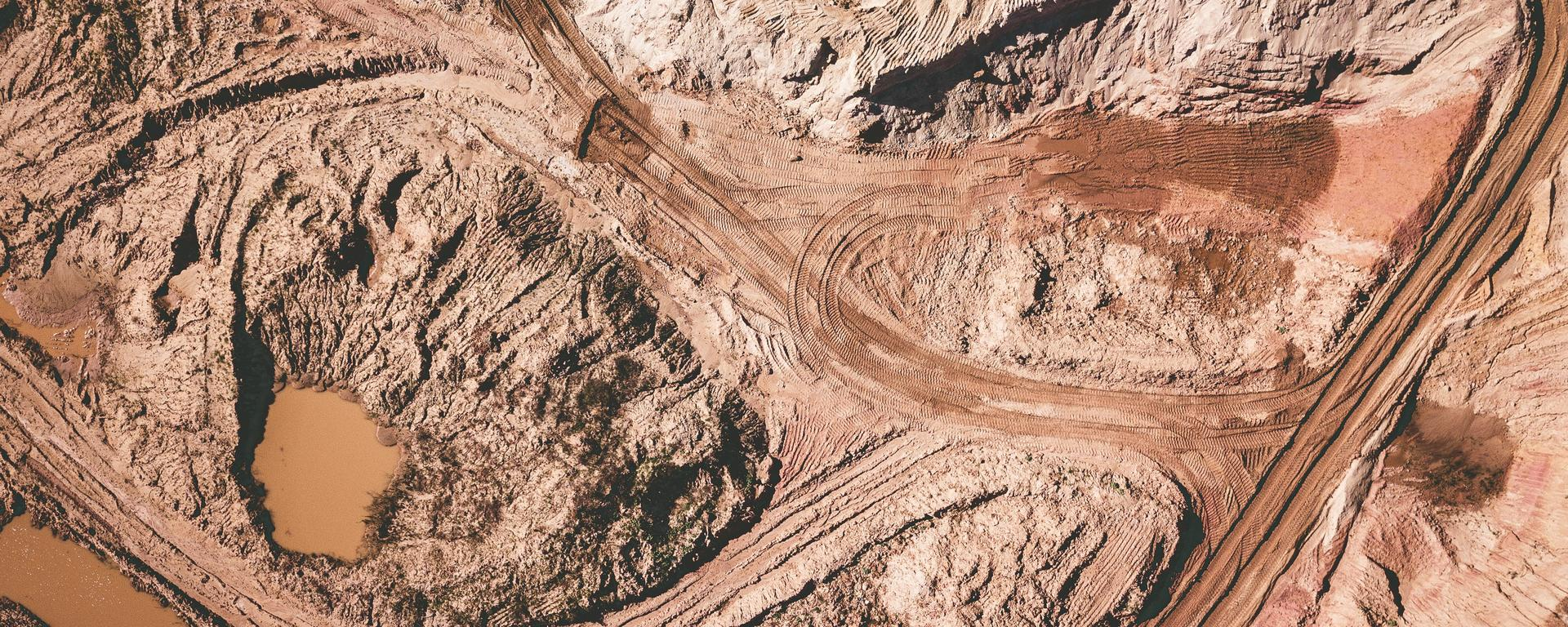 An overhead view of an open pit mine. The ground is brown and rusty-looking, and there are dirt roads leading into and out of the mining area.