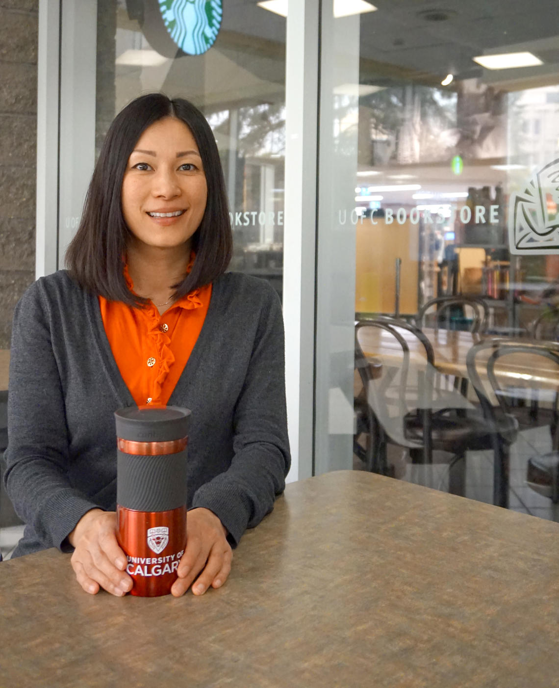 Photo of Gina Ko holding an ecofriendly mug