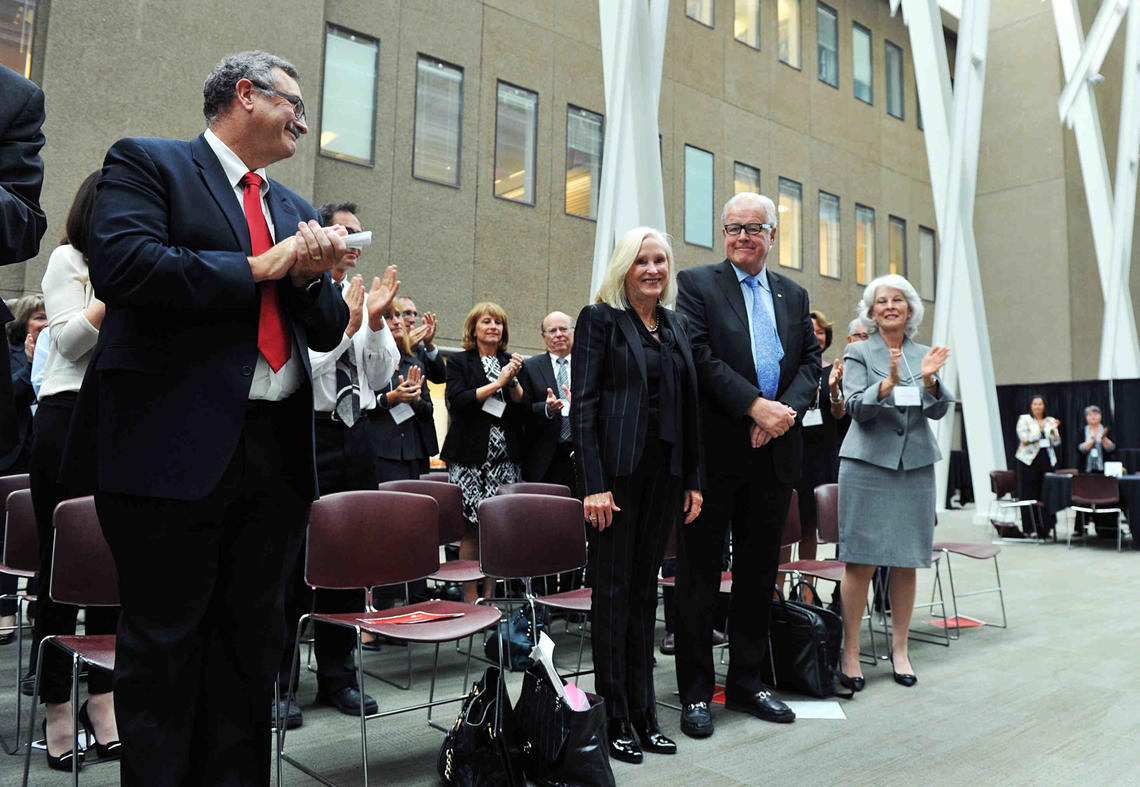 Dr. Jon Meddings, left, dean of the Cumming School of Medicine, and Bonnie DuPont, right, chair of the University of Calgary Board of Governors, join the audience in applauding the O'Briens for their generous gift Tuesday.