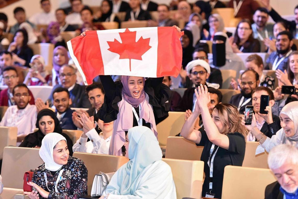 Canadian team member Heyam Abdulrahman celebrates the win, while teammate Rineem Saleh applauds.