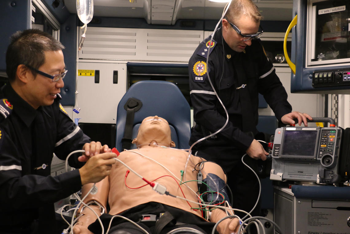 Two paramedics are working on a patient in this simulation that was part of the UCalgary/EMS study. One paramedic is wearing the eye tracking technology.