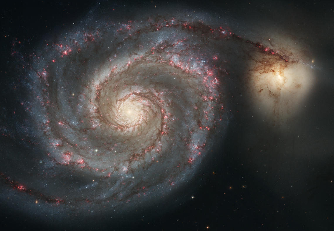 "The nearby ""Whirlpool galaxy""; spiral arms, dark dust lanes, and bright stars are visible."
