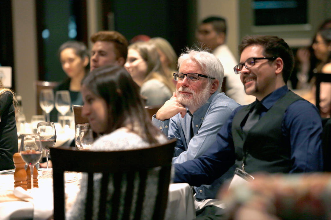 Jordan Bartsch, far right, enjoys the keynote presentation at Industry Night 2019, an event hosted at the Silver Springs Golf and Country Club by the Society of Undergraduates in Economics (SUE)