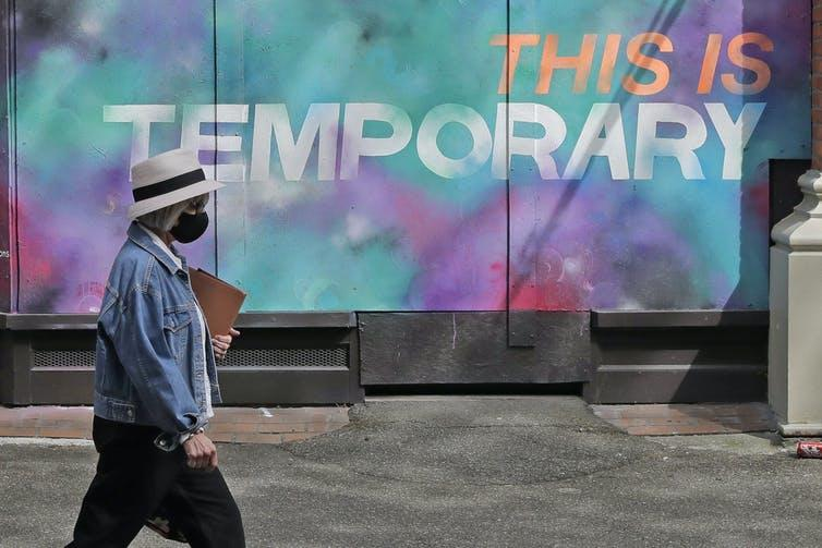A person walks by a mural on a boarded-up window on April 28, 2020, in Seattle, Wash., where public street art has sprung up all over the city.