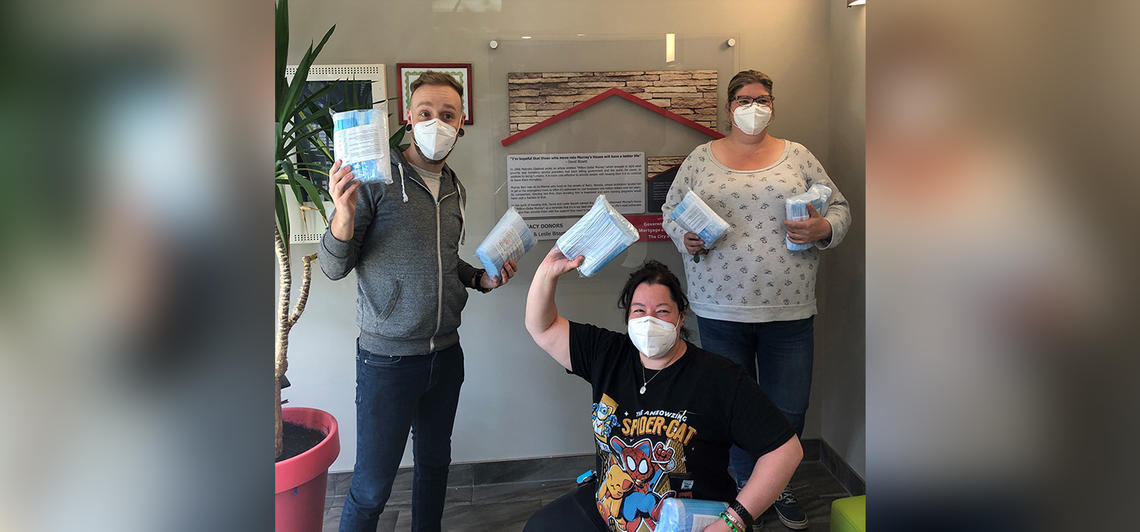 Staff at Murray's House, an independent housing facility that serves those who are chronically homeless and need health supports to live, showcase some of the PPE supplied by Street CCRED in June, 2020.