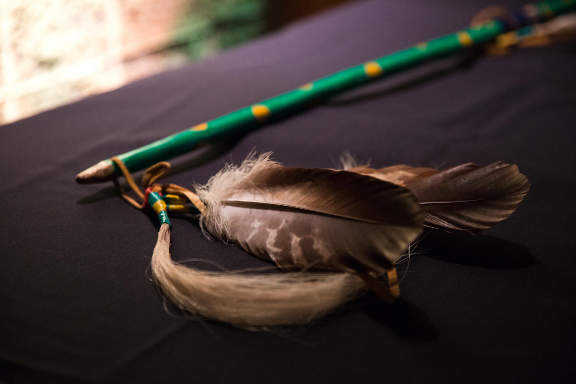 Two feathers lie on a black table top
