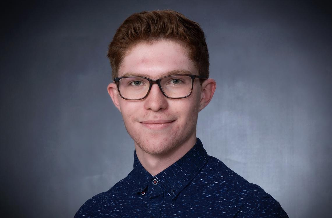 Young man with dark red hair wearing a navy button up shirt with white flecks and dark tortoiseshell glasses