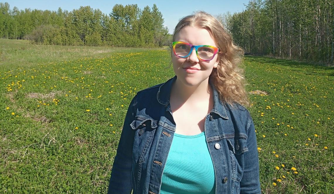 Young woman with wavy blonde hair wearing glasses with a rainbow frame, a dark wash denim jacket and bright teal shirt standing in an open green space