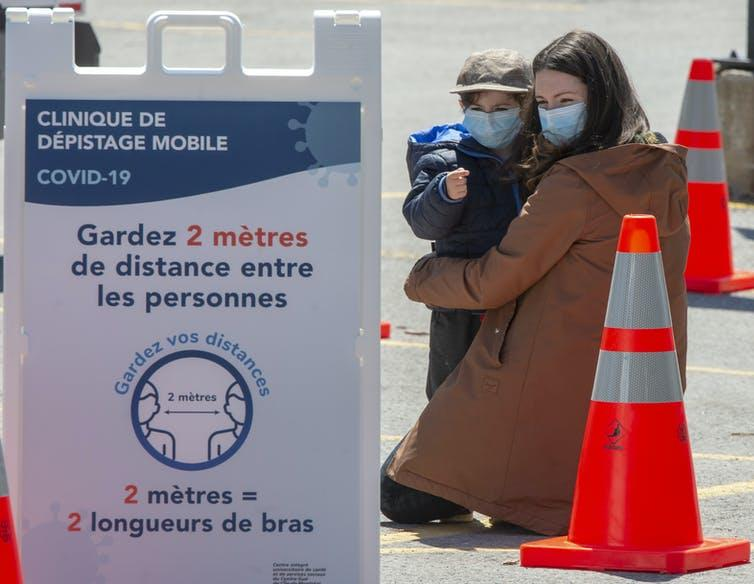 A woman and child wait in line at a mobile COVID-19 testing clinic on May 12, 2020, in Montréal.