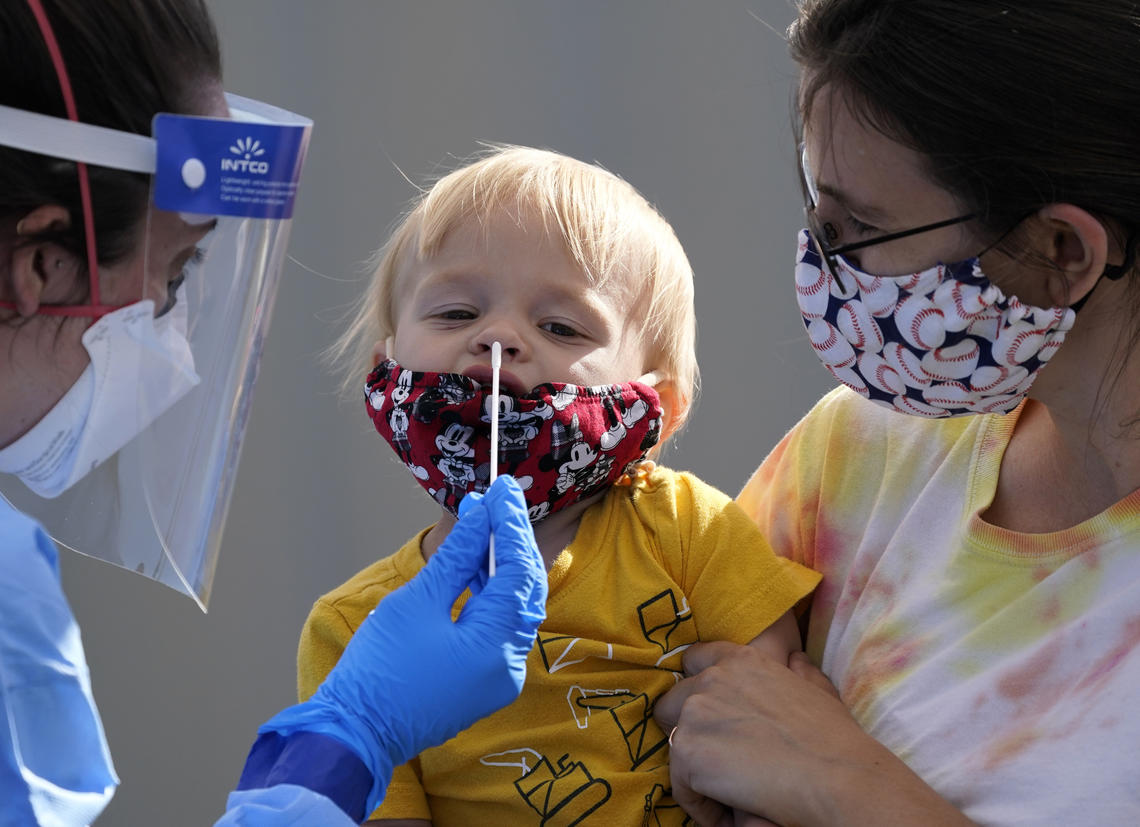 One-year-old Quentin Brown is held by his mother, Heather Brown, as he eyes a swab while being tested for COVID-19 at a new walk-up testing site at Chief Sealth High School in Seattle on Aug. 28, 2020.