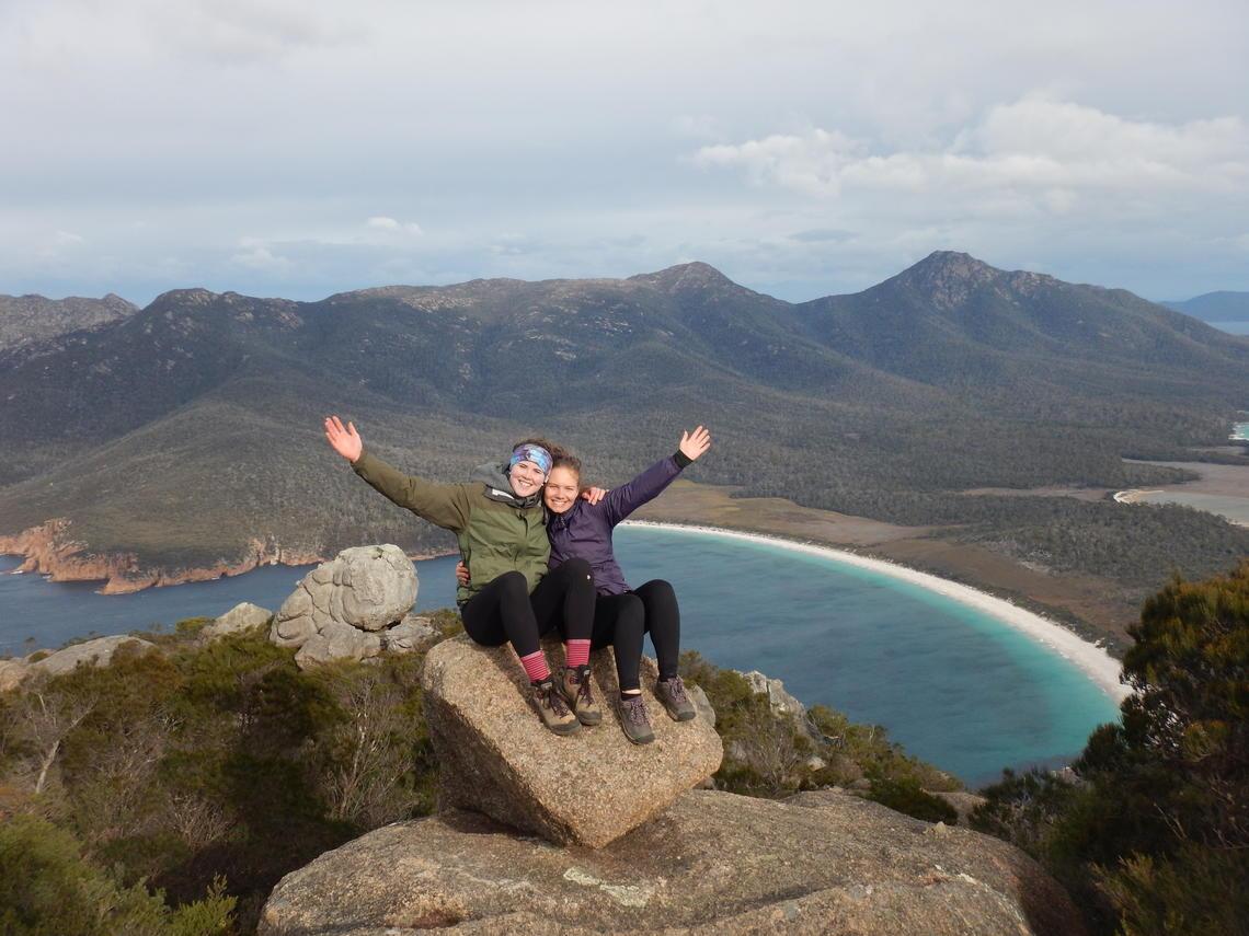 Kira Makuk (left) and her friend Grace Kennedy sit on a perch overlooking Wineglass Bay in Tasmania, Australia
