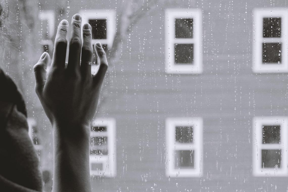 Woman pressing hand against window pain