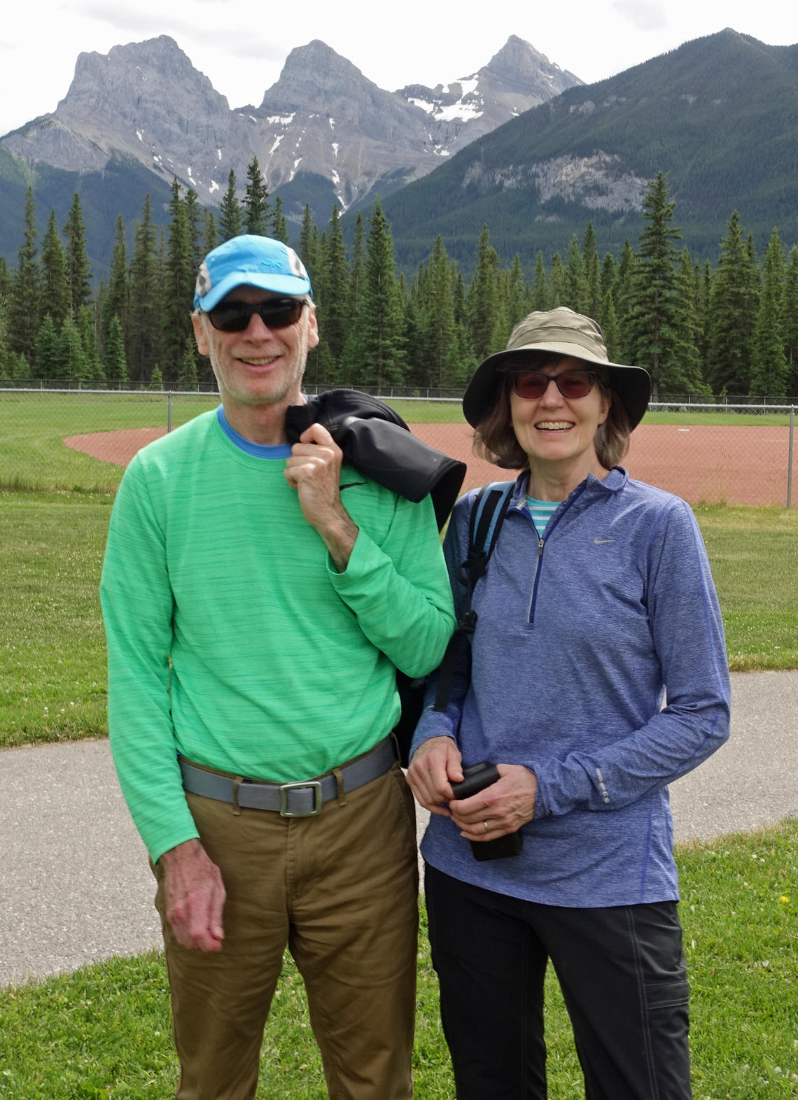 Paul and Sheena Bates stand outside in the mountains both wearing sunglasses