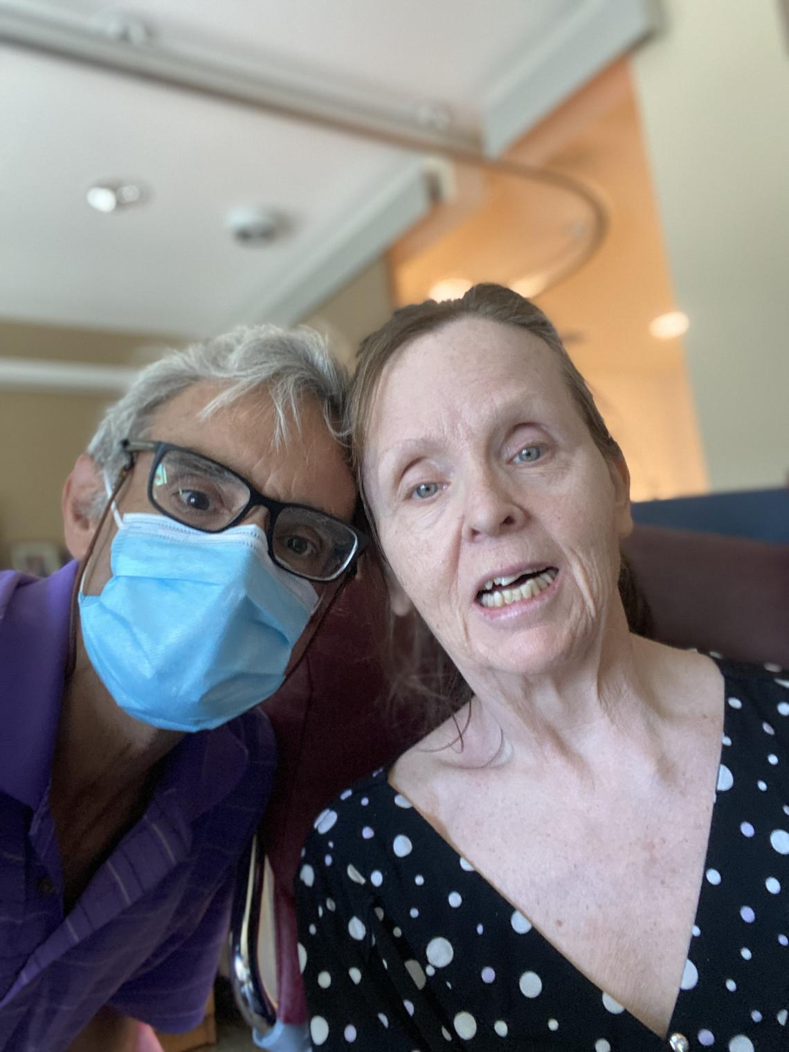 Daniel, wearing a face mask, poses next to his wife Janet who lives in a long term care facility