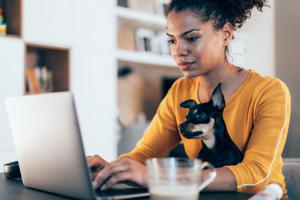 Woman with small dog typing on laptop