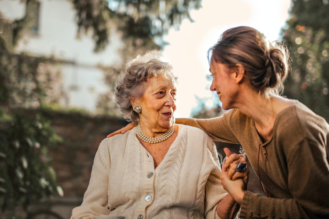 A joyful adult daughter greets her happy surprised senior mother in a garden