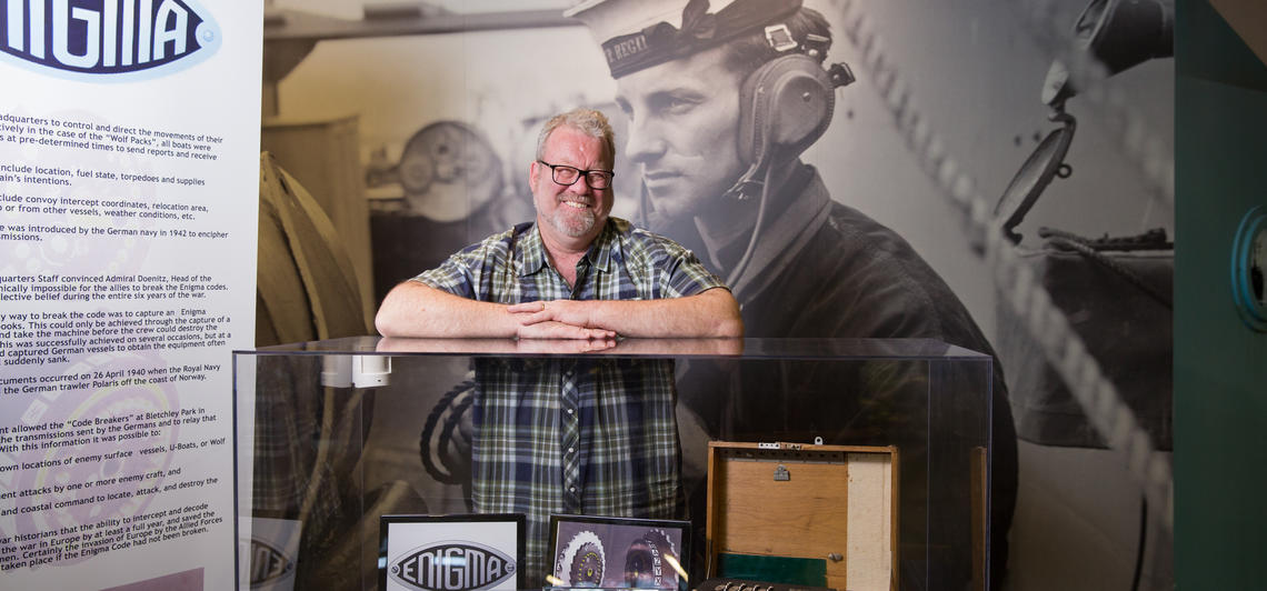 John Ferris stands in front of a display case full of historic artifacts.