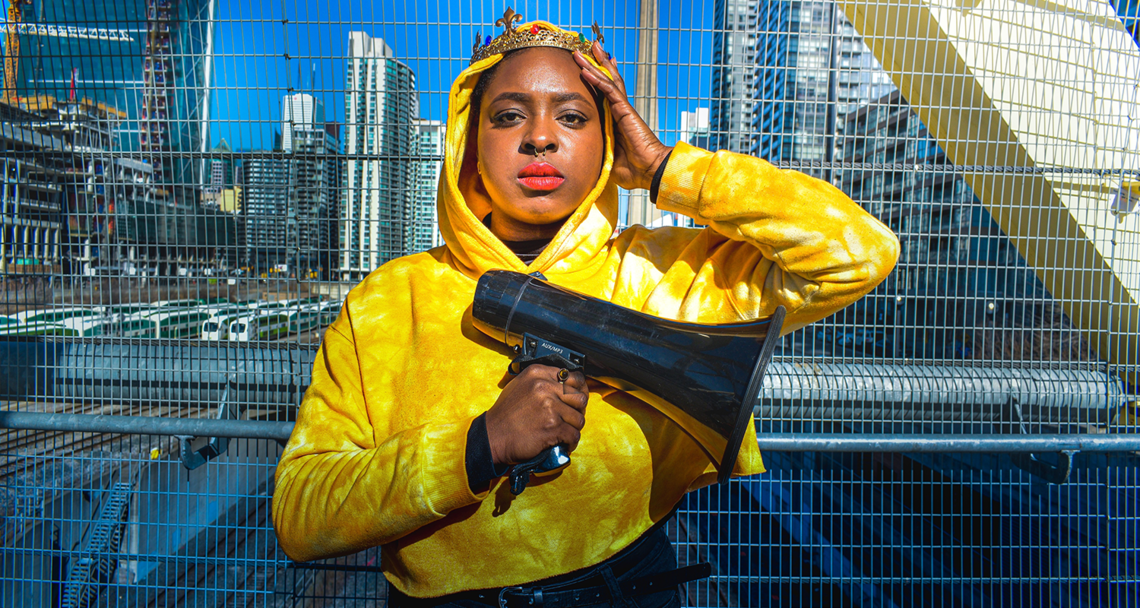 A Black woman wearing a crown and bright yellow hoodie stands against a wire fence. One hand is on her head, and the other holds a megaphone