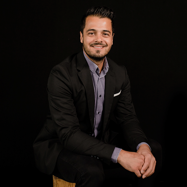 Raja Mita sits on a stool against a black background smiling. He is wearing a suit and has short hair, and a goatee