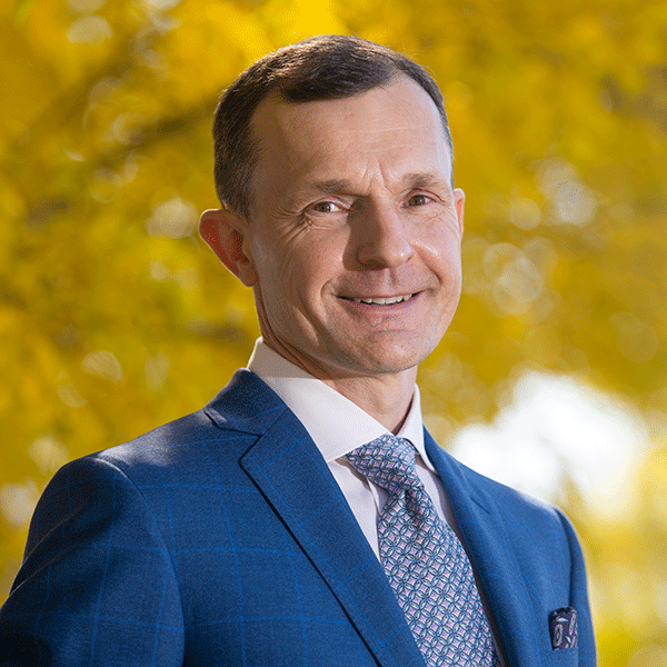 Tom Stelfox is wearing a blue suit and is smiling. He is standing outside in front of an autumnal tree.