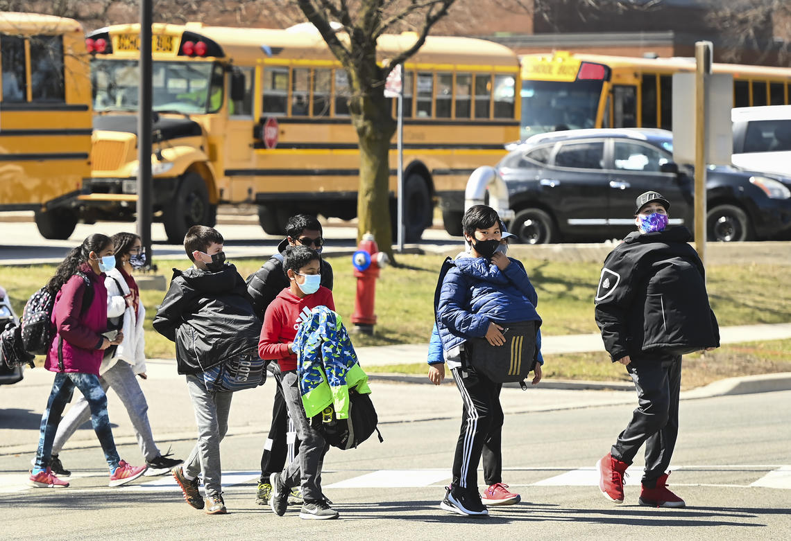 Students cross the street at Tomken Road Middle School in Mississauga, Ont., on April 1, 2021.