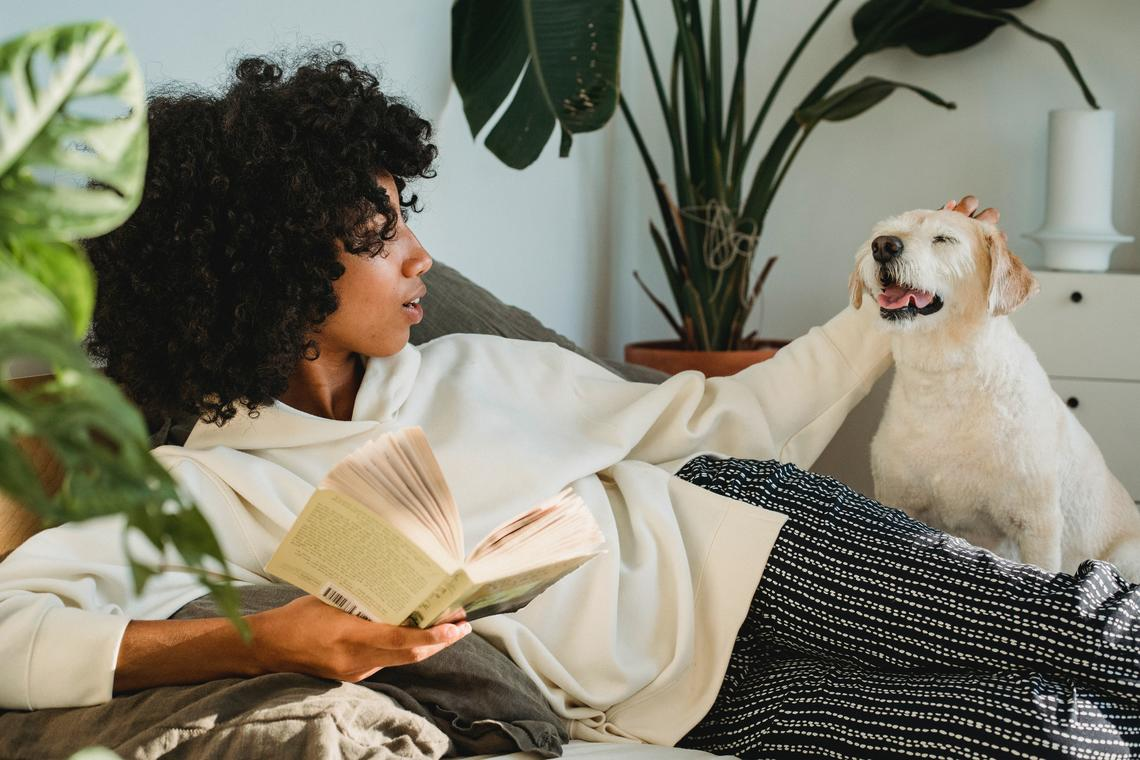 Woman pets her dog while reading a book