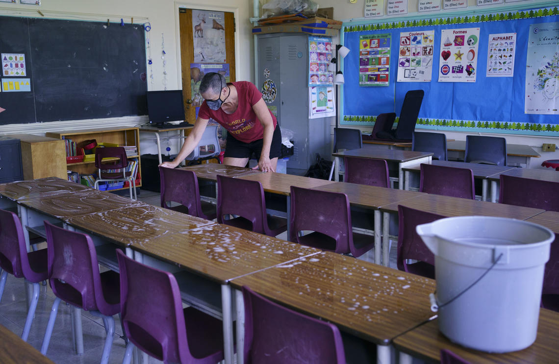 Grade two teacher Nancy Poirier washes the desks in her classroom at the Willingdon Elementary School in Montréal in August 2020.