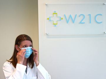 A health care provider tries on a mask in front of a sign that reads W21C