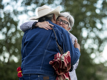 Kainai Elder Wilton Good Striker hugged Dr. Dru Marshall after sharing traditional stories with the crowd for the2nd Annual Campfire Chat at St. Patricks Island on June 21, 2017.
