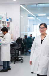 Dr. Jennifer Chan, associate professor in the Cumming School of Medicine and deputy director of the Arnie Charbonneau Cancer Institute, works alongside researchers and grad students in the new Charbonneau Cancer Institute Childhood Cancer Research Program lab. Photo by Riley Brandt, University of Calgary