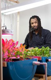 Tatenda Mambo, postdoctoral associate, Sustainability Studies, displays his aquaponics research. Photo by Riley Brandt, University of Calgary