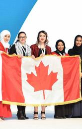 The UCalgary team accepts their silver award with a flag borrowed from the Canadian Embassy in Doha. From left: Hager Ben Mansour, Faculty of Science; Mais Abu Saleh, Faculty of Kinesiology; Rineem Saleh and Heyam Abdulrahman, Faculty of Arts; Machaille Al-Naimi, of the Qatar Foundation; Ziad Abusara, team coach from the Faculty of Kinesiology; and Hayat Abdullah Marafi, the executive director of QatarDebate. Photos courtesy Ziad Abusara