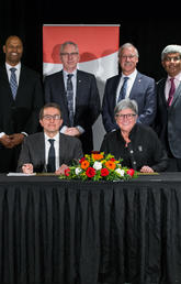 UCalgary's Dru Marshall and Mitacs' Alejandro Adem sign a collaboration agreement that facilitates international research opportunities for students. Standing, from left: Angelo Nwigwe, Oba Harding, Ed McCauley, Andre Buret, Janaka Ruwanpura and Heather Clitheroe. Photo by Adrian Shellard, for University of Calgary International