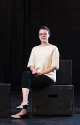 Woman sits on boxes on a stage