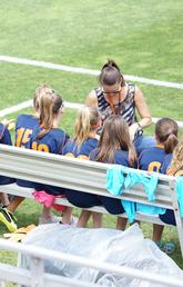 Coach talks to sports team on sidelines of field