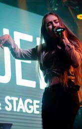 Daria Venkova (stage name Daria Purley) on stage singing.