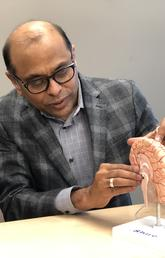 Dr. Raj Ramasubbu shows Beth MacKay where the stimulation device is place in the brain.