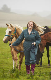 Woman leads horse in pasture