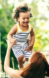 woman holding up little kid