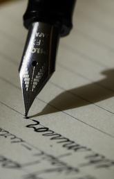 Closeup of pen nib writing on paper
