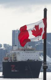 Universities face pressure to ensure their graduate programs have a clear return on investment both for students and for taxpayers. Here, the Vancouver skyline behind a Canadian flag in North Vancouver, B.C., March 24, 2020.