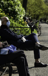 Older adult on park bench with mask on