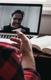 A person in a plaid shirt video chats with a male on a computer screen