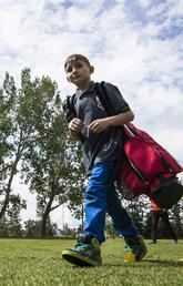 Summer camper walks across campus carrying a red golf bag