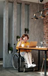 A woman in a wheelchair waving at computer screen