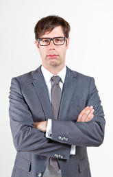 Man with glasses wearing grey suit with arms crossed