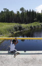 A boy sits on a bridge over a man-made channel in the First Nation of Shoal Lake 40, straddling the Manitoba/Ontario border, in June 2015. Until recently, a boil-water advisory had been in place in the community for more than 20 years despite its relative close proximity to Winnipeg