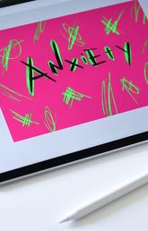 """Tablet with """"Anxiety"""" spelled out on the screen on a colourful design"""