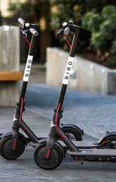 three e-scooters parked outside a building