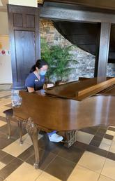 Wang playing piano at Tudor Manor for residents